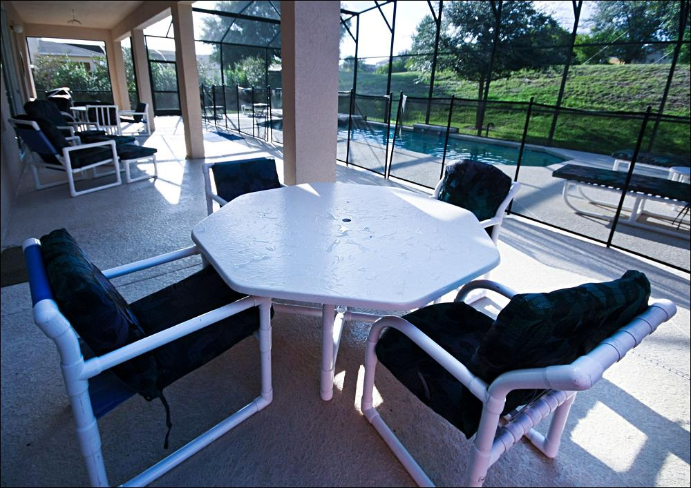 Back lanai w/ 2 tables/16 chairs by pool